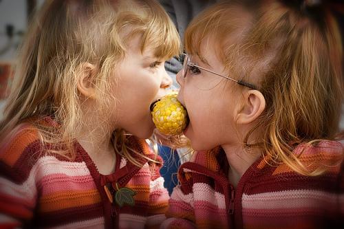 Twins Sharing Corn