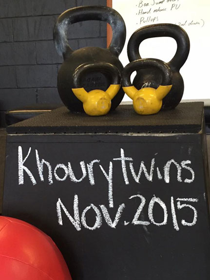 Crossfit twins pregnancy announcement with kettlebells