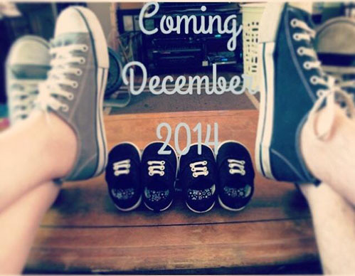 Pair of baby shoes with parents' feet to announce twin pregnancy